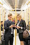 Businessman and businesswoman texting, London Underground, UK