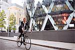 Businesswoman on bike passing 30 St Mary Axe, London, UK