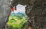 Female climber at treasure cave in Yangshuo, Guangxi Zhuang, China