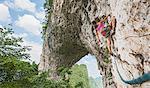 Female climber climbing on Moon Hill limestone arch in Yangshuo, Guangxi Zhuang, China