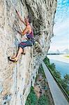 Side view of Male climber at Riverside crag in Yangshuo, Guangxi Zhuang, China