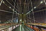 Brooklyn bridge walkway and distant Manhattan financial district skyline at night, New York, USA