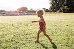 Female toddler running in field