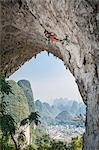 Male climber climbing the route Lunatic on Moon Hill in Yangshuo, Guangxi Zhuang, China