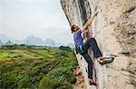 Male climber climbing at white Mountain - a limestone cliff in Yangshuo, Guangxi Zhuang, China