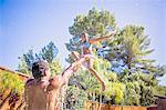 Father throwing daughter in air in swimming pool, splashing, smiling
