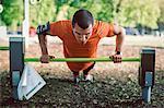 Man doing push-ups on railing at park