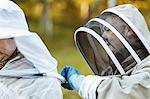 Beekeeper assisting colleague in wearing headwear at field