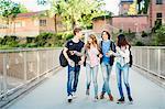 Happy teenagers enjoying while walking on bridge