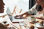 Women using laptop computer in coffee shop
