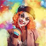 Joyful and smiling clown between multi-colour powders