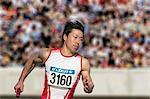 Japanese male sprinter running on track