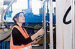 Female engineer using a digital tablet and examining the machine in an industrial plant, Freiburg Im Breisgau, Baden-Württemberg, Germany