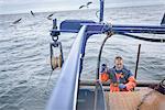 Fisherman preparing net on trawler