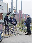 Urban cyclists chatting near factory