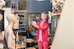 Mature woman examining china pot in vintage shop