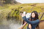 Female tourist taking smartphone selfie at Skogafoss waterfall, Iceland