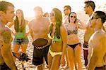 Adult friends with American football ball on Newport Beach, California, USA