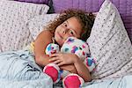 Girl lying in bed cuddling teddy bear looking at camera