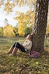 Girl sitting under tree in park