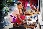 Woman placing religious offering on doorstep at a Balinese wedding, Petulu Village near Ubud, Bali, Indonesia