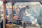 Men cooking in outdoor kitchen, Penglipuran, traditional Balinese village, Bangli, Bali, Indonesia