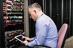 Technician using tablet in server room