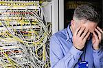 Stressed technician working on broken server