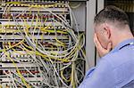 Stressed technician looking at open server locker