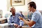 Caretaker taking senior man's blood pressure