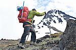 Male mountain climber walking uphill, rear view, Chugach State Park, Anchorage, Alaska, USA