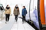 Full length of happy school friends walking on railroad platform