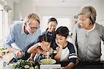 Family looking at girl preparing food at kitchen counter