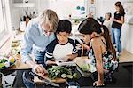 Grandfather and children preparing food in kitchen