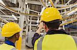 Workers discussing printing press conveyor belts overhead