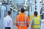 Workers and supervisor standing in factory corridor