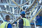 Workers looking up at winding printing press conveyor belts overhead