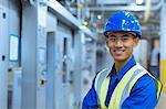 Portrait smiling worker in hard-hat in factory