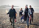 Multi-generation family walking on sunny beach