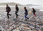Family running on rocky beach