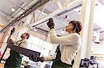 Workers hanging steel part in factory