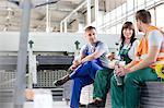 Workers enjoying coffee break in factory