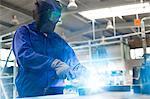 Welder in protective workwear using welding torch in steel factory