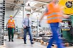 Engineer and works walking in factory
