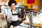 Waitress serving cappuccino to camera