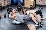Muscular couple doing bosu ball exercises