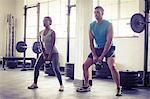 A muscular couple lifting kettlebells