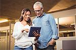 Businesswoman explaining colleague over digital tablet