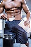 Fit shirtless man scooping protein powder