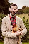Smiling man holding chicken